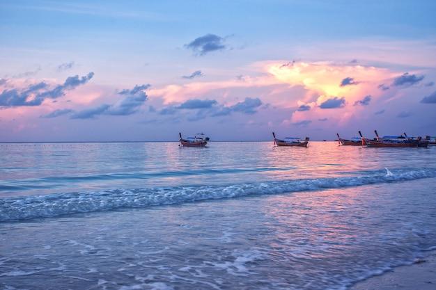 Деревянные рыбацкие лодки на морском пляже в утреннем восходе солнца