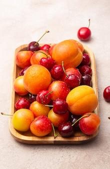 Деревянная плоская тарелка со свежей вишней, сливами и абрикосами с каплями воды