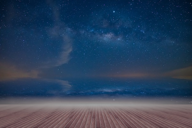 Wooden floor and backdrop of the milky way sky at night