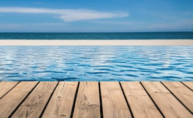 Деревянный пол с пейзажным бассейном на фоне пляжа