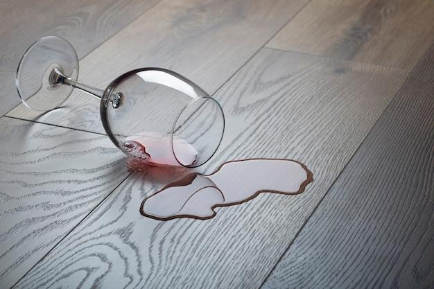 Деревянный пол с перевернутым бокалом красного вина. пролитое вино на деревянный ламинат (паркет) с влагозащитой.