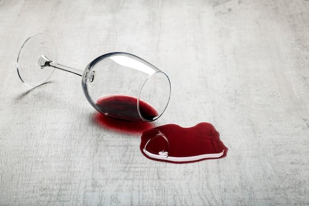 나무 바닥에 뒤집힌 레드 와인 한 잔이 나무 라미네이트에 엎질러진 와인