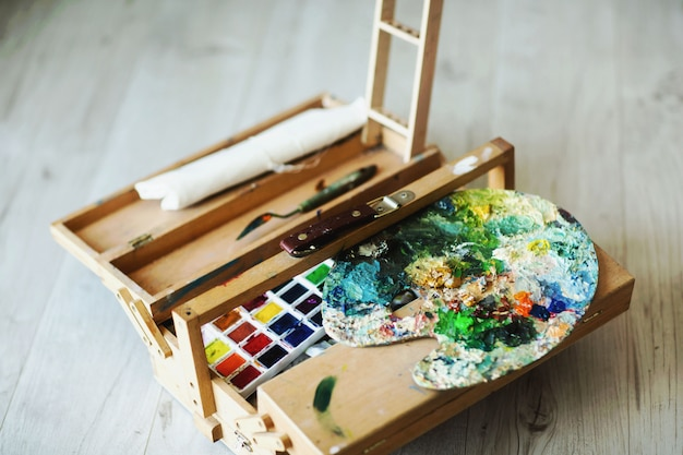 Wooden folding suitcase artist with brushes, paint and palette.