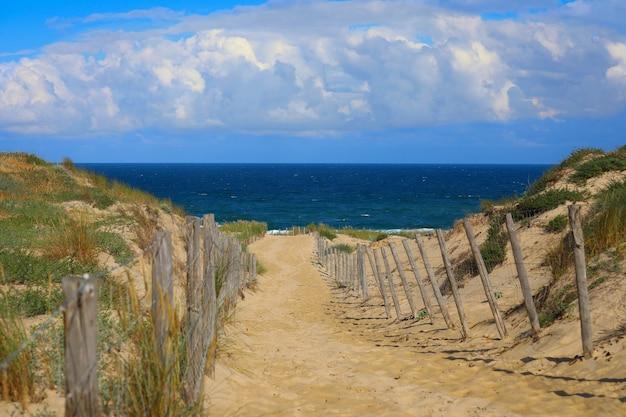 美しい日に砂浜への木製の歩道の道