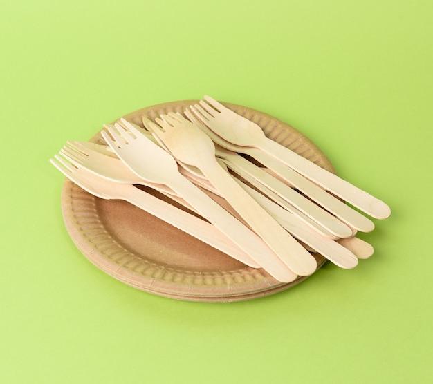 Деревянная вилка и пустая круглая одноразовая тарелка коричневого цвета из переработанных материалов на зеленом фоне, вид сверху. концепция отсутствия неперерабатываемого мусора, отказ от пластика