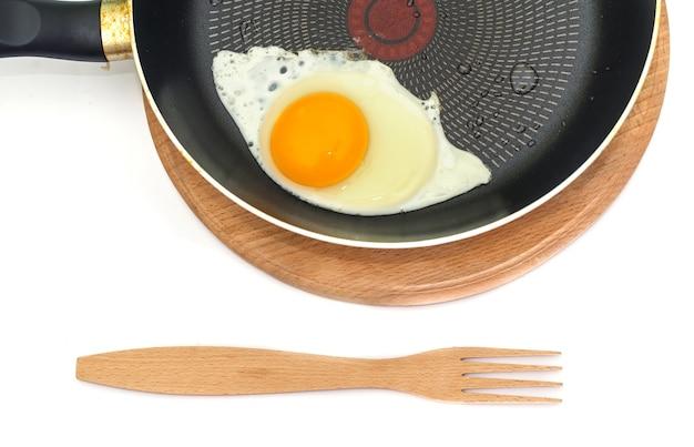 白のフライパンに木製フォークと目玉焼き。フライパンの一部