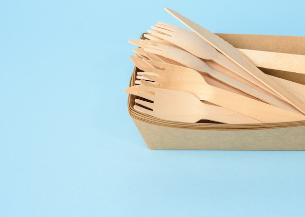 Wooden fork and empty brown disposable plate made from recycled materials on a blue background, top view. concept of the absence of non-recyclable garbage, rejection of plastic