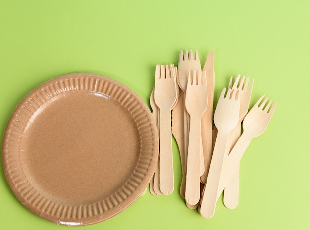 Wooden fork and empty round brown disposable plate made from recycled materials on a green background, top view. concept of the absence of non-recyclable garbage, rejection of plastic