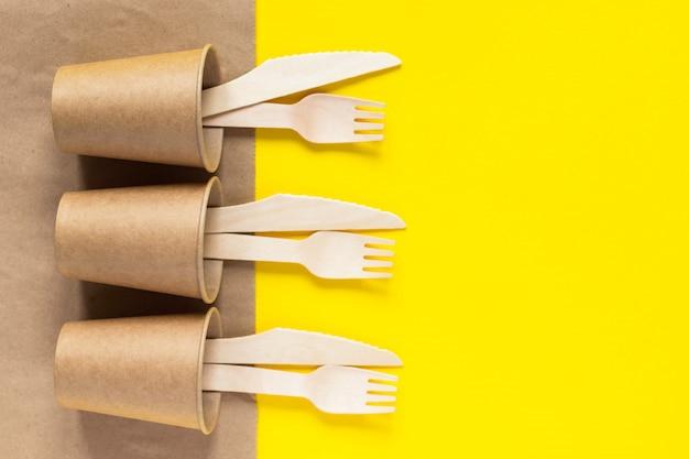 Деревянные вилки и ножи, крафт бумажный стаканчик и сумка на желтом фоне