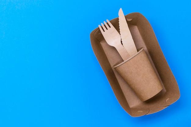 Деревянные вилки и ножи, чашка в крафт-бумаги на синем фоне