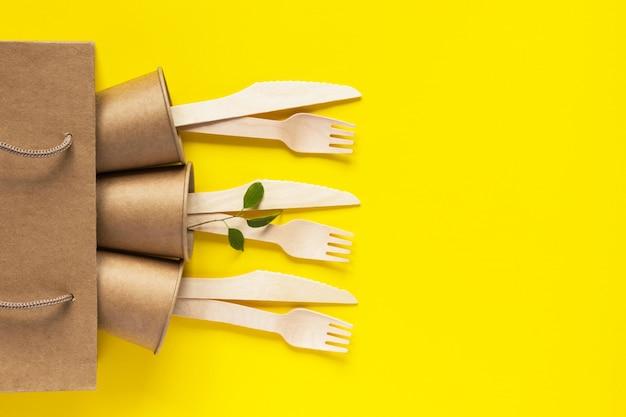 Деревянные вилки и ножи, бумажный стаканчик в ремесленной сумке на желтом фоне