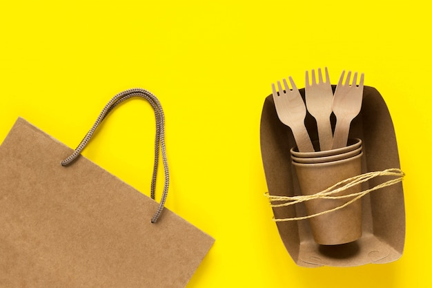 Wooden forks and cups in craft paper plate and bag yellow background