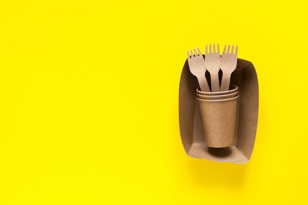 Деревянные вилки в крафт-бумаги на желтом фоне