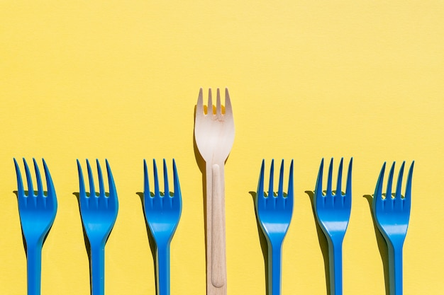 Wooden forks in a row on yellow