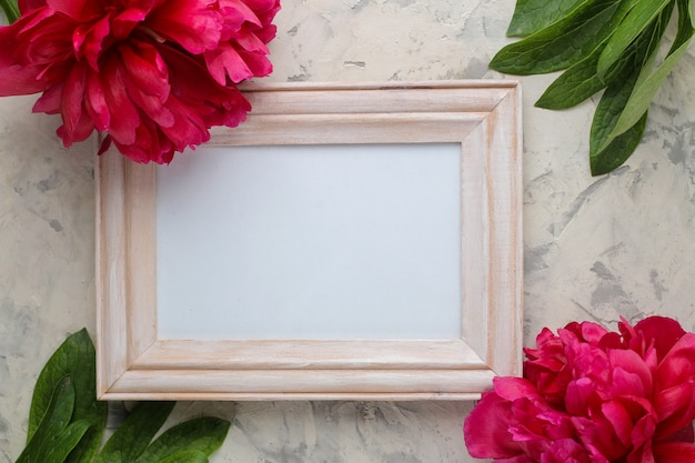 Wooden frame and beautiful bright pink flowers peonies on a light concrete background. top view. space for text
