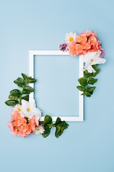 Wooden frame decorated with flowers on a blue pastel background. top view mockup with copy space.