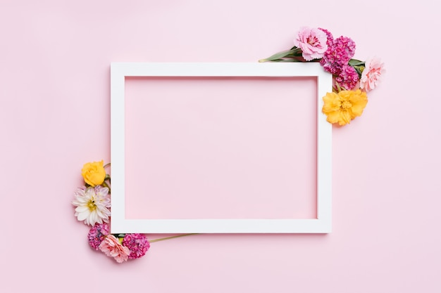 Wooden frame decorated with flowers on a pink pastel background. top view mockup with copy space.