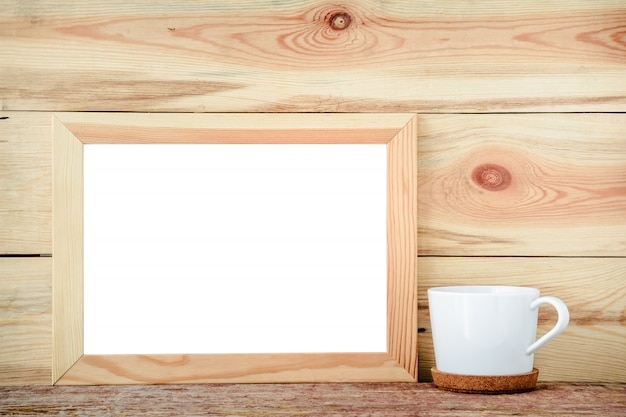 Wooden frame isolated with decorations from a white cup on a wooden background.