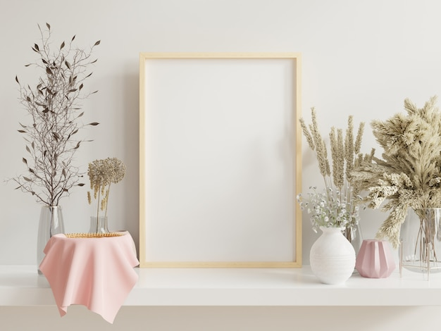 Wooden frame leaning on white shelf in bright interior with plants on the table with plants in pots on empty wall