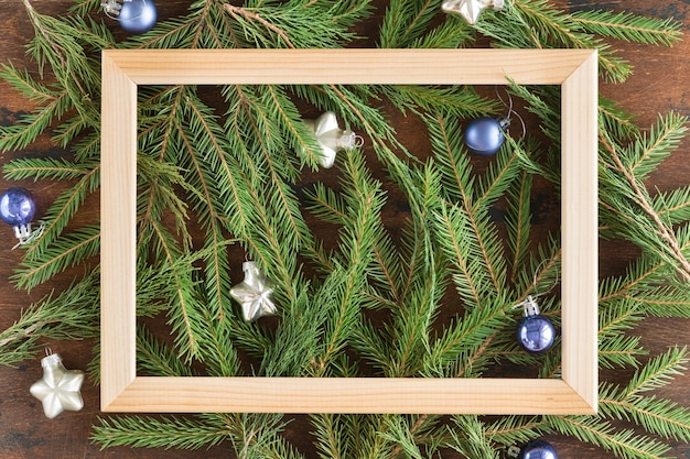 Wooden frame made of fir tree branches and christmas decorations on dark wooden background
