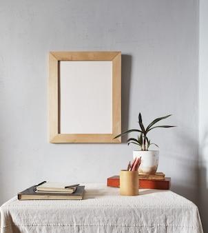 Макет деревянного каркаса. скандинавский минималистичный дизайн. горшок на стопке книг на старом деревянном столе. композиция на белой поверхности стены