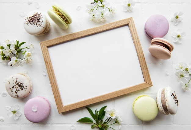 Wooden frame mockup with  macaroons  and spring blossom on tile surface