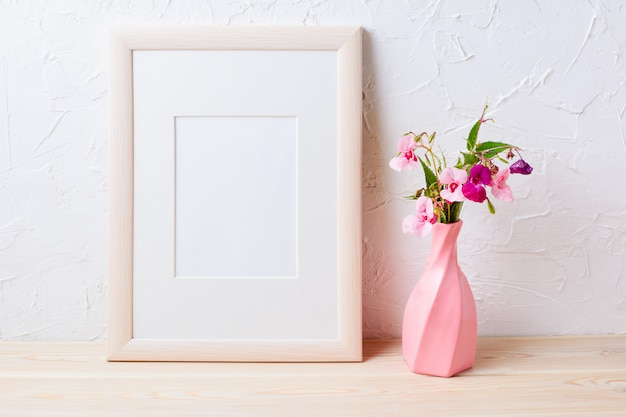 Wooden frame mockup with purple wildflowers in pink vase