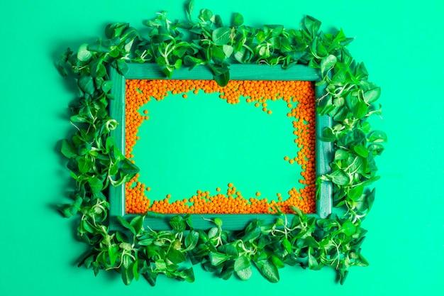 トウモロコシのサラダとcopyspaceのミントターコイズのオレンジ色のレンズ豆の木製フレーム