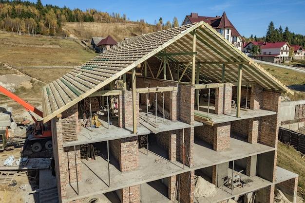 建設中のレンガの大きな家に新しい屋根の木製フレーム。