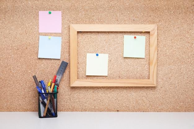 Деревянная рамка на пробковой доске и карандаши в держателе