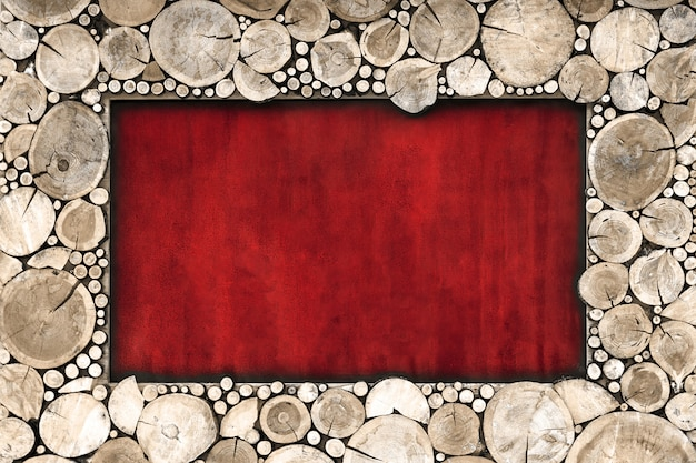 Wooden frame of sawn wood brown color on a red background.