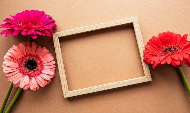 Wooden frame surrounded by beautiful gerbera flowers on a light brown background, top view, copy space, flat lay.