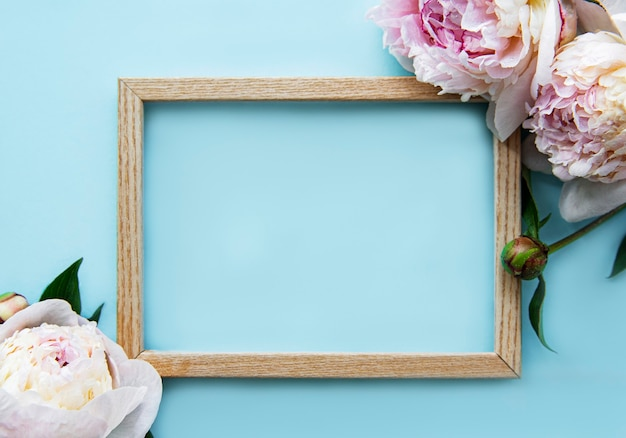 Wooden frame surrounded by beautiful pink peonies on a blue surface, top view, copy space, flat lay