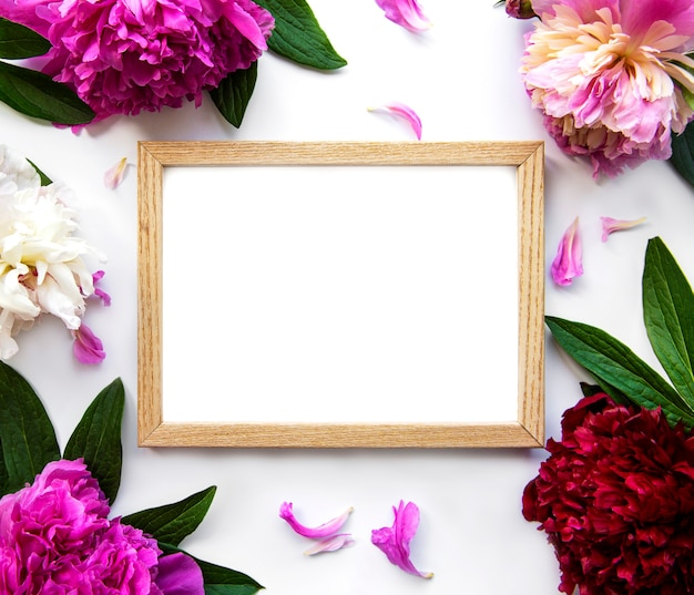Wooden frame surrounded by beautiful pink peonies on a white background
