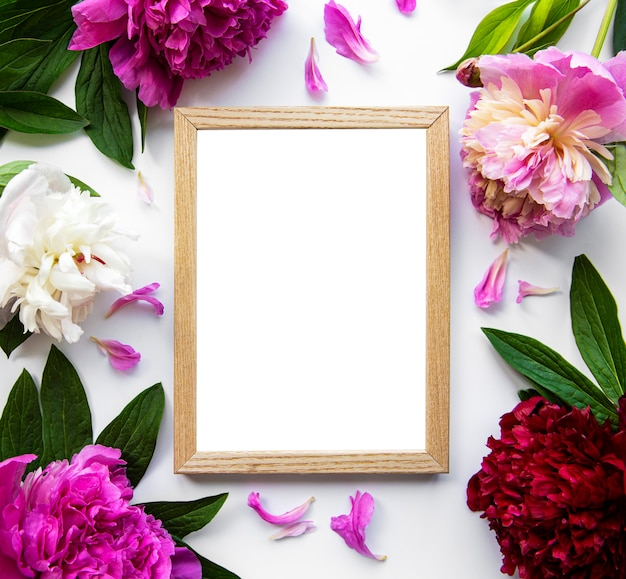 Wooden frame surrounded by beautiful pink peonies on a white surface, top view, copy space, flat lay