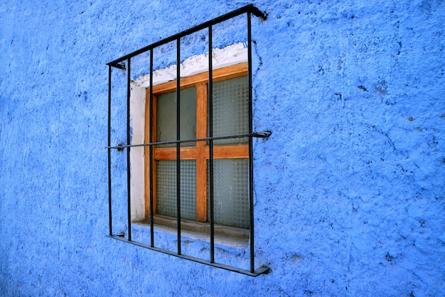 Wooden frame window on vivid blue colored stone wall