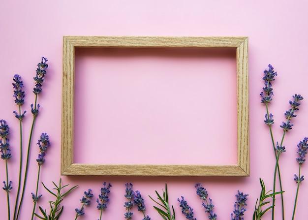 ピンクの背景に香りのよいラベンダーの美しい花と木製フレーム