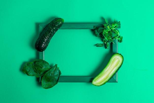 Деревянная рамка с огурцами, шпинатом и кукурузным салатом