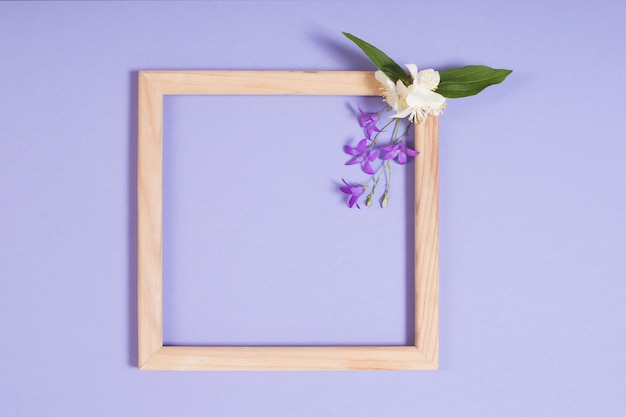 Wooden frame with flowers on purple paper