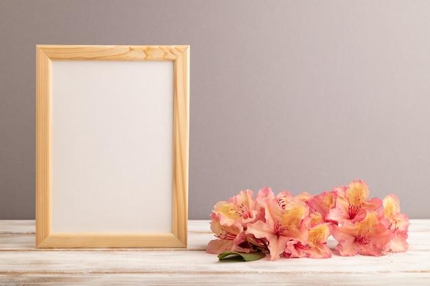 灰色のパステル背景にピンクのツツジの花と木製フレーム。側面図、コピースペース、
