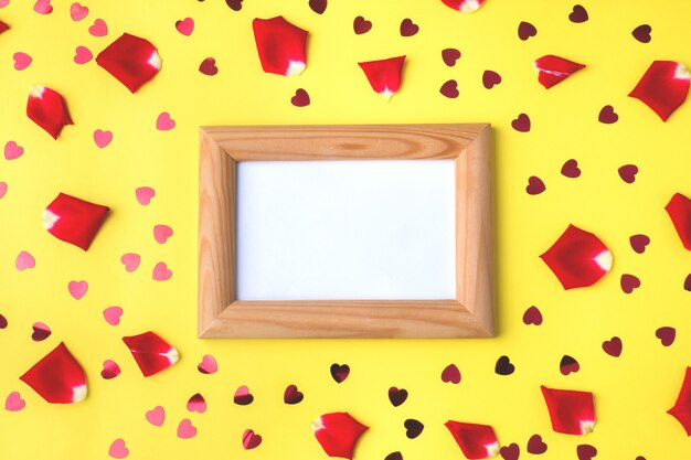 Wooden frame with space for text, rose petals and red hearts.