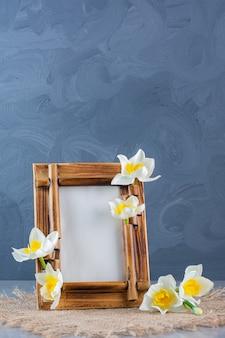 Cornice in legno con fiori bianchi su tela di sacco.