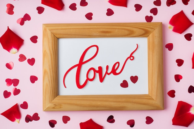 Wooden frame and the word love, rose petals and red hearts.