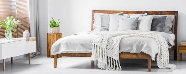 Удобная кровать с деревянным каркасом, множеством подушек, одеяла, простыней и буфетом с цветами наверху в белом стильном интерьере спальни. реальное фото. панорама.