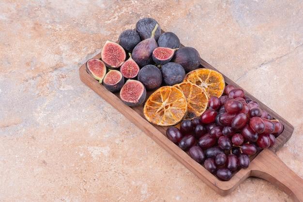 Piatto di frutta in legno con fichi, bacche d'angolo e fette d'arancia secche.