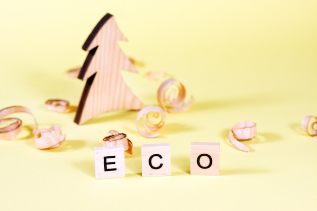 Wooden fur-tree, curled shavings and word eco on yellow.