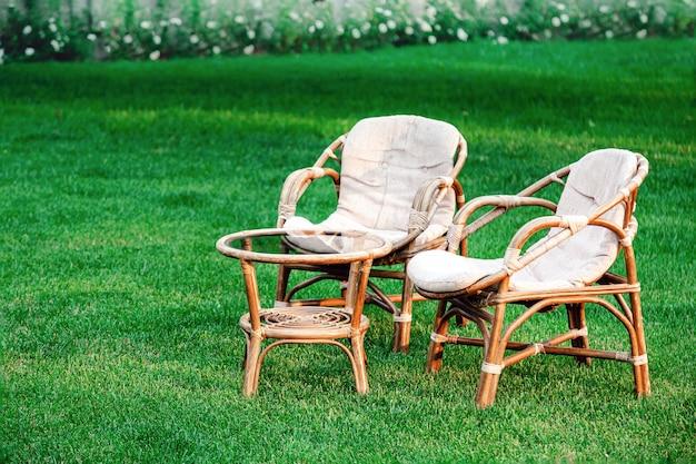 夏の暑い日にリラックスできる屋外の芝生の上の木製ガーデン家具。自然の中のバラと 2 つの椅子のある庭の風景。パークカフェで一休み。裏庭の外観。誰も。