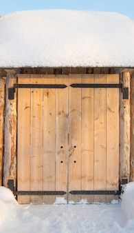 Wooden gate in the fence on a sunny winter day