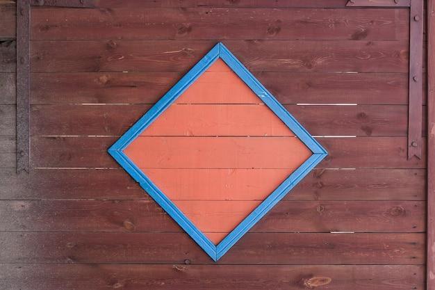 Деревянные ворота из старых выцветших красных досок с оранжевым квадратом