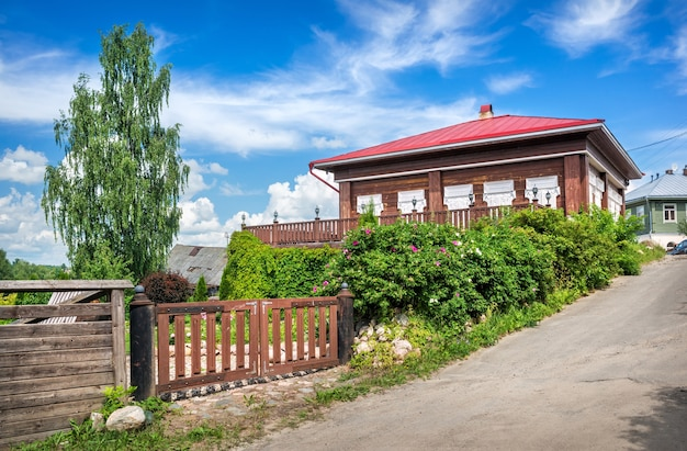 Wooden gate near a house with windows in plyos under a blue sky with white clouds on a summer sunny day